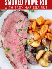 Slice of prime rib on plate with roasted vegetables