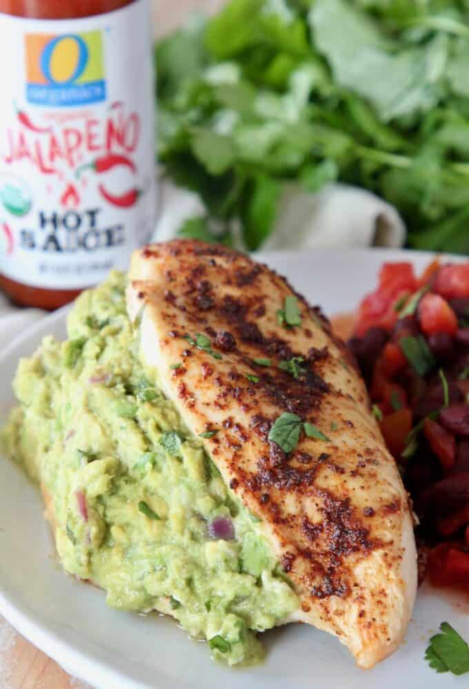 guacamole stuffed chicken breast on plate with black beans
