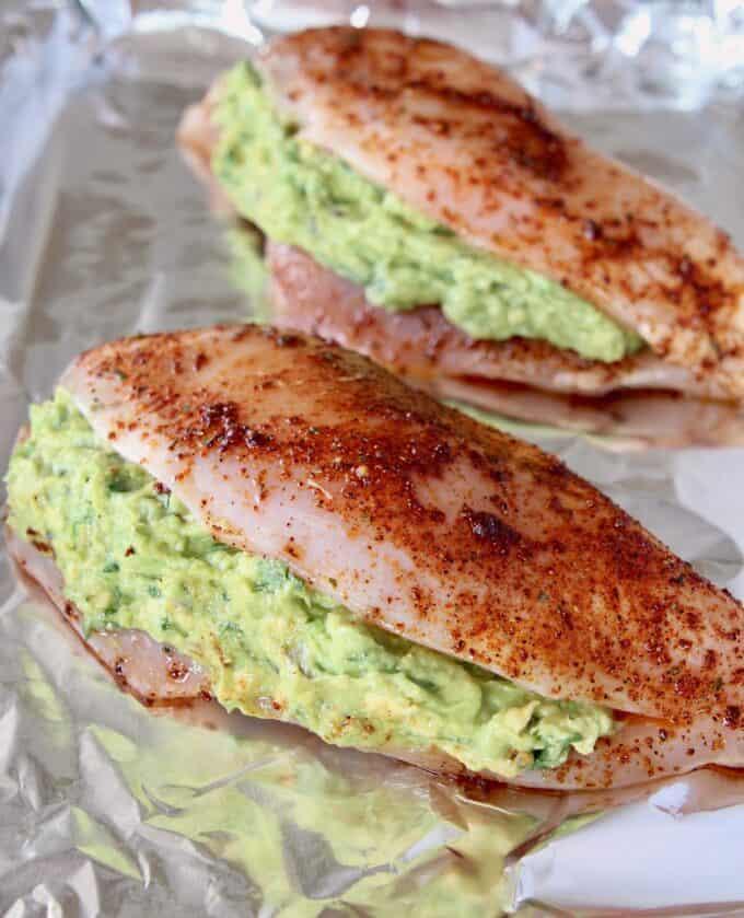 Uncooked guacamole stuffed chicken on foil-lined baking sheet