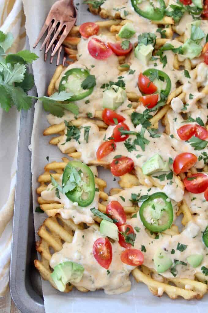 overhead image of waffle fries on baking sheet covered in cheese sauce