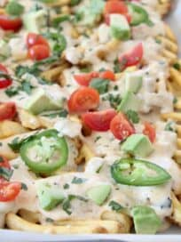 waffle fry nachos topped with sliced jalapenos and diced tomatoes