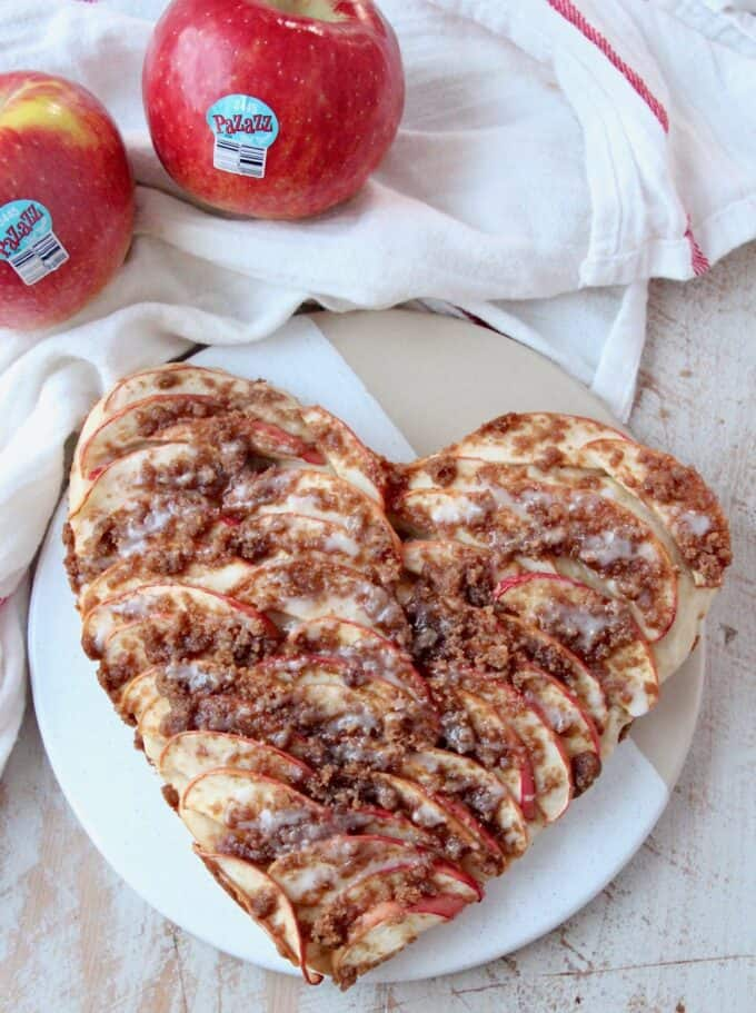 overhead image of heart shaped apple pizza on serving dish with fresh apples on the side