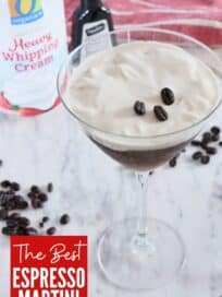 espresso martini topped with whipped cream in martini glass