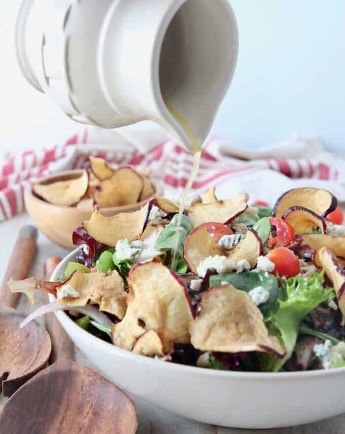 small pitcher pouring salad dressing onto salad in bowl