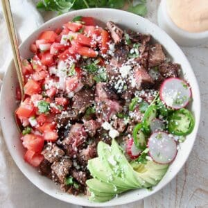 diced carne asada in bowl with avocado and pico de gallo