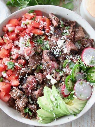 diced carne asada in bowl with avocado and pico de gallo