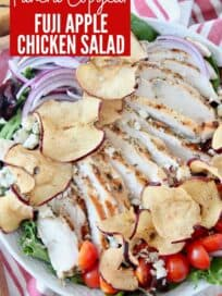 sliced chicken on top of salad in bowl with apple chips