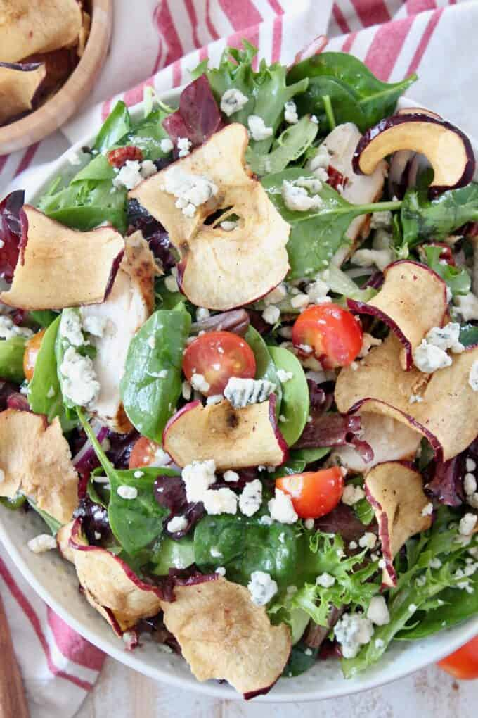 salad in bowl tossed with apple chips and gorgonzola cheese
