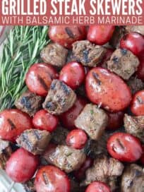 grilled cubes of sirloin on skewers with red potatoes stacked up on a plate with rosemary sprigs