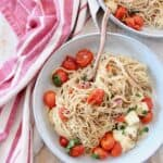 cooked angel hair pasta in bowl with cherry tomatoes, basil and mozzarella cheese
