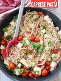 caprese pasta in skillet with red serving spoon with fresh basil on the side