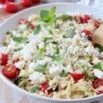 orzo salad with tomatoes, mint and feta in white bowl