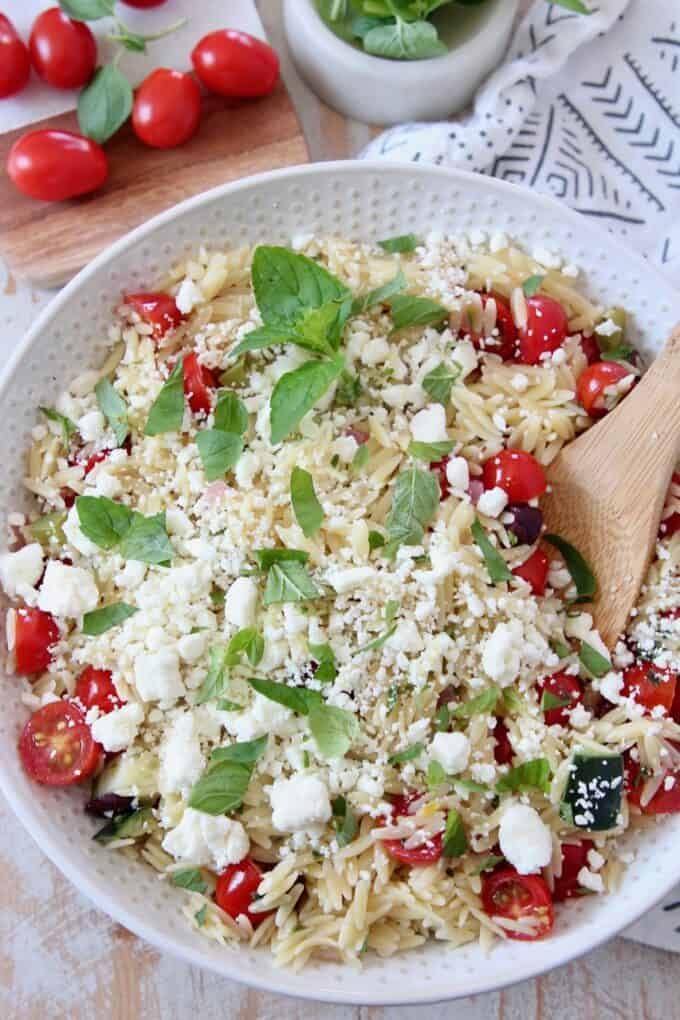 greek orzo salad in bowl with wooden spoon