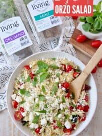 greek orzo salad in bowl with wooden spoon with herbs and grape tomatoes on the side