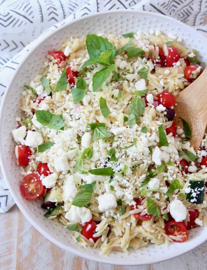 orzo salad with tomatoes and feta in bowl with wooden spoon